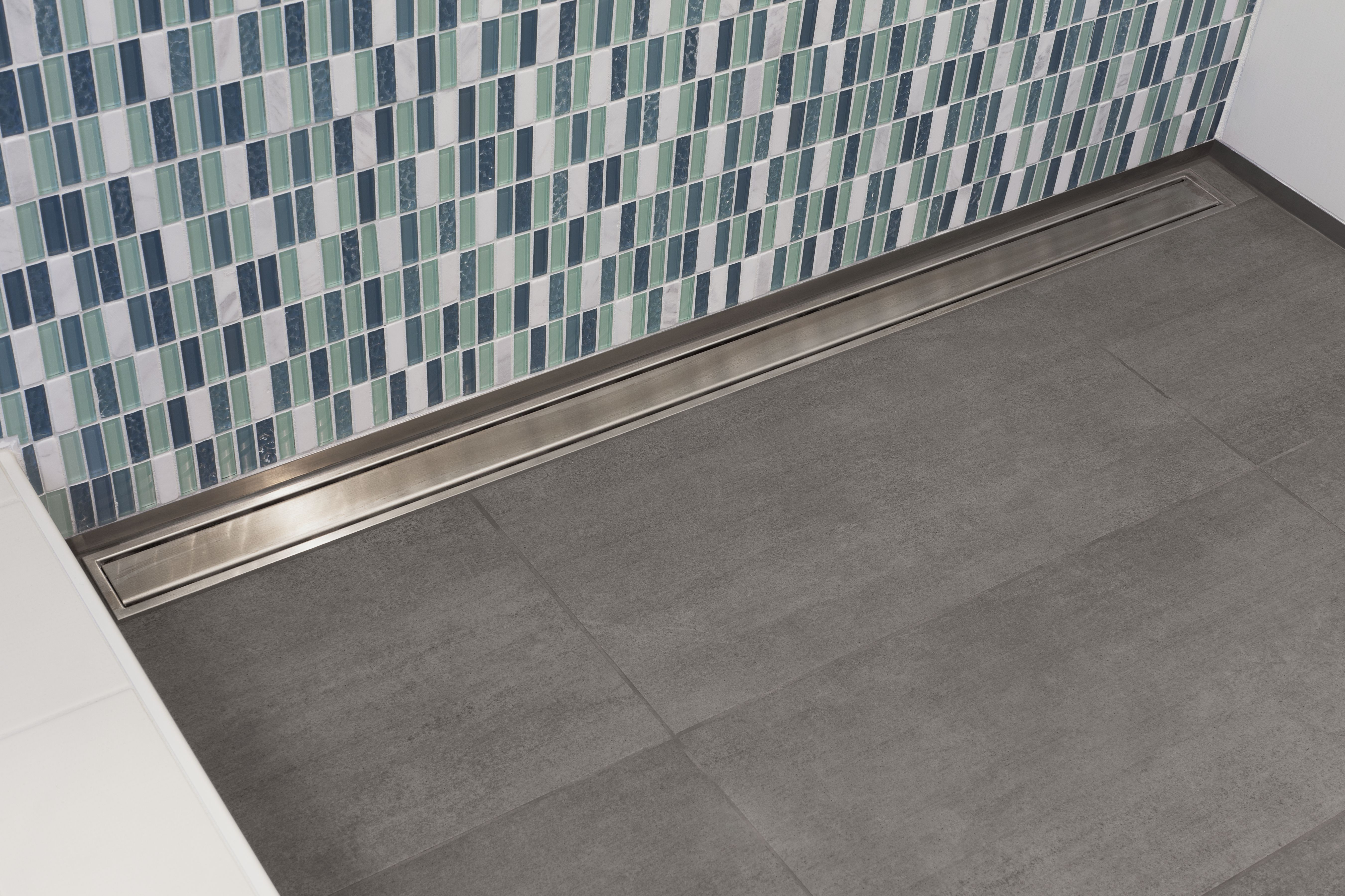 Blue lagoon schluter kerdi line linear drain allows for the use of large format tile on the shower floor while adding a real touch of elegance in this shower the solid dailygadgetfo Gallery